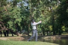 A mostra do homem dos jogadores de golfe bateu varrer no gramado verde Imagens de Stock Royalty Free