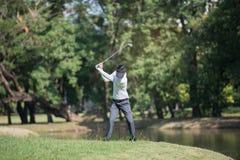 A mostra do homem dos jogadores de golfe bateu varrer no gramado verde Imagens de Stock