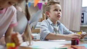 Mostra do menino o que fez com tesouras e papel colorido com c?mera do fluxo video estoque