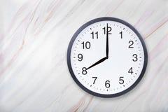 Mostra do pulso de disparo de parede oito horas na textura de mármore Mostra 8pm ou 8am do pulso de disparo do escritório fotografia de stock royalty free