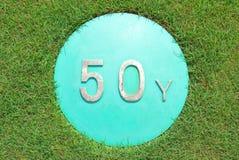 A mostra do sinal uma distância de 50 jardas no campo de golfe verde Fotos de Stock