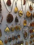 Mostra dos pendentes das mulheres bonitas feitos do âmbar fotografia de stock