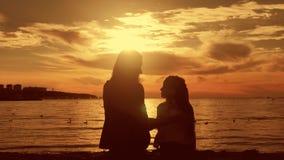 Mostra em silhueta a mãe e a filha senta-se na praia no por do sol Conceito da família amigável, estilo de vida filme