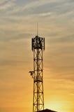 Mostra em silhueta a torre da telecomunicação em uma laranja woderful Foto de Stock