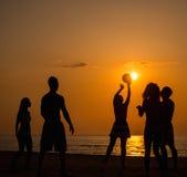 Mostra em silhueta um jovem em uma praia fotografia de stock