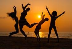 Mostra em silhueta um jovem que tem o divertimento em uma praia Foto de Stock Royalty Free