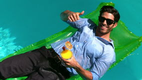 Mostra felice dell'uomo d'affari pollici su nella piscina stock footage
