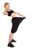 Mostra felice quanta peso ha perso, grandi pantaloni della donna Fotografia Stock