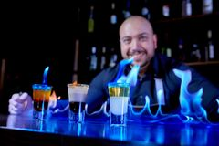 Mostra impetuosa na barra O barman faz o cocktail alcoólico quente e inflama a barra O barman prepara um cocktail impetuoso foto de stock royalty free