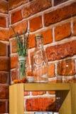Mostra-janela na loja dos cosméticos no fundo do tijolos vermelhos Em garrafas de vidro do apoio de madeira e flores e ervas viol imagens de stock