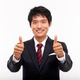 Mostrando a pollice il giovane uomo asiatico di affari. Immagini Stock Libere da Diritti