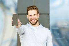 Mostrando seu telefone esperto brandnew Barba do homem com smartphone, fundo urbano Homem com mostras de sorriso felizes da cara  Imagem de Stock
