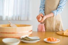 Mostrar cómo hacer la bola de arroz `` Onigiri `` es una comida típica en Japón El pueblo japonés ase un poco de arroz en bolas c imagenes de archivo
