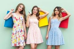 Mostrar tarjetas de crédito Muchachas atractivas en el vestido, colocándose delante de fondo verde Imagenes de archivo