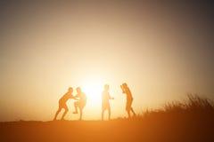 Mostre em silhueta as crianças que jogam no tempo feliz do por do sol do verão Foto de Stock