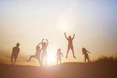 Mostre em silhueta as crianças que jogam no tempo feliz do por do sol do verão Imagem de Stock