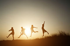Mostre em silhueta as crianças que jogam no tempo feliz do por do sol do verão Imagens de Stock
