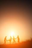 Mostre em silhueta as crianças que jogam no tempo feliz do por do sol do verão Imagem de Stock Royalty Free