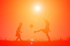 Mostre em silhueta as crianças que jogam o futebol no por do sol do céu Tempo sobre Foto de Stock