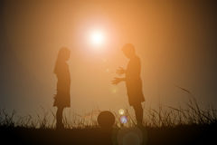 Mostre em silhueta as crianças que jogam o futebol no por do sol do céu Tempo sobre Fotografia de Stock Royalty Free