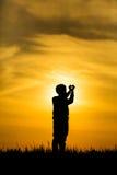 Mostre em silhueta as mãos do menino que fazem um coração no por do sol Imagens de Stock