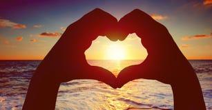 Mostre em silhueta as mãos na forma do coração com por do sol no meio e no fundo da praia Fotografia de Stock Royalty Free
