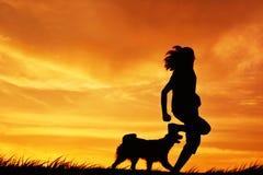 Mostre em silhueta as mulheres e o cão que jogam no por do sol do céu Imagens de Stock