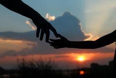 Mostre em silhueta as posses do pai a mão de uma criança Imagens de Stock Royalty Free