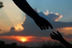 Mostre em silhueta as posses do pai a mão de uma criança Imagem de Stock