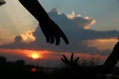 Mostre em silhueta as posses do pai a mão de uma criança Imagens de Stock