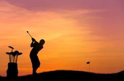 Mostre em silhueta a bola de golfe da batida do jogador de golfe do menino para o furo no por do sol Imagens de Stock