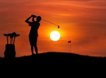 Mostre em silhueta a bola de golfe da batida do jogador de golfe do menino para o furo no por do sol Fotografia de Stock Royalty Free
