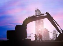 Mostre em silhueta carregadores e trabalhador da construção em um terreno de construção ov Fotos de Stock