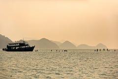 Mostre em silhueta a cena do turista que pega fora o barco à praia no ko Chang, Tailândia fotos de stock royalty free
