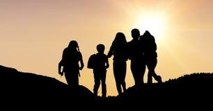 Mostre em silhueta crianças com as trouxas contra o céu durante o por do sol Fotografia de Stock