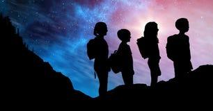 Mostre em silhueta crianças com as trouxas contra o céu na noite Imagem de Stock Royalty Free