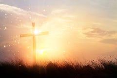 Mostre em silhueta a cruz cristã na grama no fundo m do nascer do sol imagens de stock