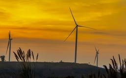 Mostre em silhueta a exploração agrícola da turbina eólica sobre o moutain com por do sol alaranjado e Imagem de Stock Royalty Free