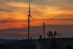 Mostre em silhueta a exploração agrícola da turbina eólica sobre o moutain com por do sol alaranjado e Fotos de Stock