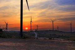 Mostre em silhueta a exploração agrícola da turbina eólica sobre o moutain com por do sol alaranjado e Foto de Stock Royalty Free