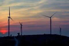 Mostre em silhueta a exploração agrícola da turbina eólica sobre o moutain com por do sol alaranjado e Imagem de Stock