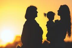 Mostre em silhueta a família com a mãe, a filha e a avó exteriores Por do sol no parque Fotografia de Stock
