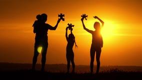 Mostre em silhueta a família feliz que joga no campo no tempo do por do sol Povos que têm o divertimento na natureza Uma parte do filme