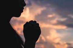 Mostre em silhueta fora da jovem mulher que reza para bênçãos do ` s do deus com th imagem de stock