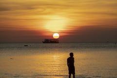 Mostre em silhueta a fotografia do homem na praia do mar contra o sol bonito Fotos de Stock