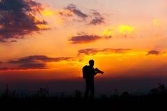 Mostre em silhueta a fotografia do por do sol da fotografia o peop alaranjado do por do sol Fotos de Stock
