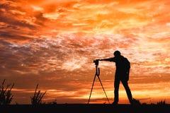 Mostre em silhueta a imagem de um fotógrafo com um fundo do por do sol Fotografia de Stock