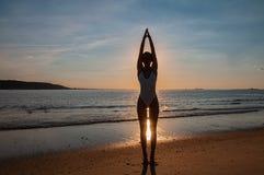Mostre em silhueta a ioga da mulher na praia no por do sol A mulher está praticando a ioga no por do sol na costa de mar fotos de stock royalty free