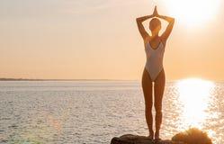 Mostre em silhueta a ioga da mulher na praia no por do sol A mulher está praticando a ioga no nascer do sol na costa de mar fotografia de stock royalty free