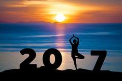 Mostre em silhueta a ioga do jogo da jovem mulher no mar e nos 2017 anos ao comemorar o ano novo feliz Fotografia de Stock